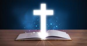 Abra la Sagrada Biblia con brillar intensamente cruzado en el centro Fotos de archivo