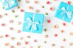Abra las cajas de regalo azules con las rosas rosadas en el fondo blanco Fotografía de archivo
