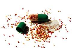 Abra las píldoras de la cápsula aisladas en blanco Fotos de archivo libres de regalías