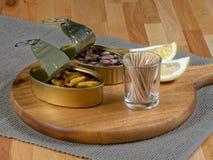 Abra latas de lata dos mexilhões e do polvo em uma placa de madeira rústica Imagens de Stock Royalty Free