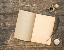 Abra los materiales de oficina del libro y del vintage del diario en la tabla de madera Fotografía de archivo libre de regalías