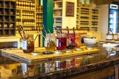 Abra los tarros del atasco de diversas frutas preparadas para probar en una pequeña tienda de vino imágenes de archivo libres de regalías