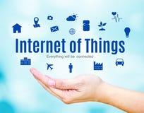 Abra a mão com Internet das coisas (IoT) palavra e ícone no fundo azul do borrão imagem de stock