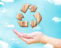 Abra a mão fêmea com reciclam o ícone de madeira do sinal com céu azul e c Fotografia de Stock Royalty Free
