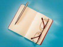 Abra a nota, a pena e os monóculos na opinião superior de papel azul imagens de stock