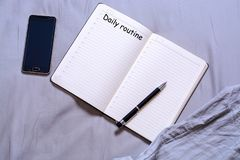 Abra o bloco de notas com a pena preta com a inscrição e o lugar para mentiras do texto na cama com um smartphone O conceito de f Imagem de Stock
