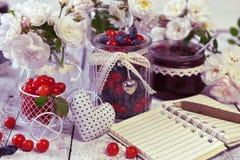 Abra o caderno com espaço da cópia, frascos do vintage com a baga da cereja e de mel e doce caseiro Imagem de Stock