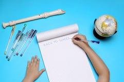 Abra o caderno com flauta, globo e mãos da menina caucasiano Fotografia de Stock