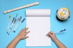 Abra o caderno com flauta, globo, folhas de outono e mãos da menina caucasiano Imagens de Stock