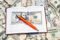 Abra o caderno com fundo dos dólares Fotos de Stock