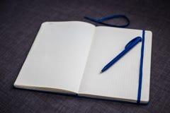 Abra o caderno com pena azul fotografia de stock royalty free