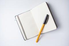 Abra o caderno com uma laranja ballpen nela Fotografia de Stock Royalty Free