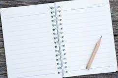 Abra o caderno e o lápis vazios no fundo de madeira Imagens de Stock Royalty Free