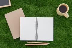 Abra o caderno e o lápis no campo de grama imagem de stock royalty free