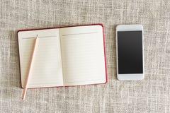 Abra o caderno e o smartphone no pano de saco limpo com lápis de madeira Fotografia de Stock