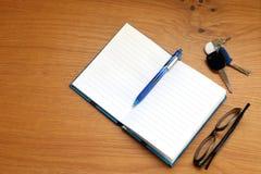 Abra o caderno e a pena, monóculos, chaves em uma tabela Imagens de Stock Royalty Free