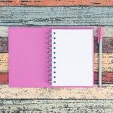 Abra o caderno e a pena roxos na tabela de madeira do vintage para o fundo e o texto Fotos de Stock Royalty Free