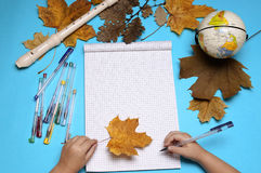 Abra o caderno, a flauta, o globo, as folhas de outono e as mãos da menina caucasiano Fotos de Stock