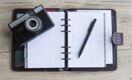 Abra o caderno marrom com uma câmera da pena e da foto no fundo de madeira Livro Branco Tabela de madeira Zombaria acima Caderno  Fotos de Stock Royalty Free