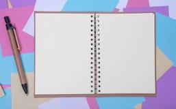 Abra o caderno no fundo de etiquetas coloridas Imagens de Stock Royalty Free