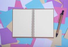 Abra o caderno no fundo de etiquetas coloridas Foto de Stock