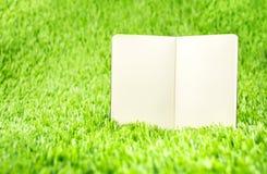 Abra o caderno no tem da grama verde, do conceito do negócio e da educação Fotos de Stock