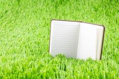 Abra o caderno no tem da grama verde, do conceito do negócio e da educação Fotos de Stock Royalty Free