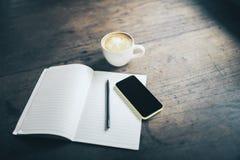 Abra o caderno, a pena, o telefone celular e a xícara de café vazios em de madeira Fotografia de Stock Royalty Free