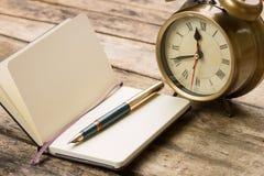 Abra o caderno pequeno com pena de fonte e o despertador antiquado atrás Fotografia de Stock Royalty Free
