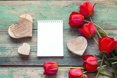 Abra o caderno vazio com tulipas vermelhas e corações decorativos em velho Foto de Stock