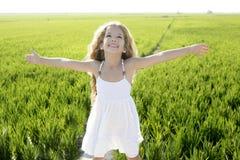 Abra o campo feliz pequeno do prado do verde da menina dos braços Imagens de Stock Royalty Free