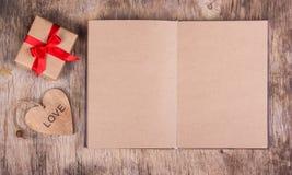 Abra o diário com páginas vazias do papel reciclado, da caixa de presente com uma curva e de um coração de madeira Copie o espaço Foto de Stock Royalty Free