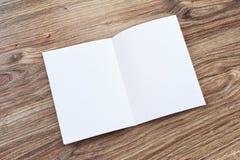 Abra o folheto vazio, compartimento está em uma mesa de madeira fotografia de stock