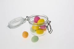 Ovos de chocolate coloridos no frasco de vidro Fotos de Stock Royalty Free