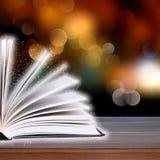 Abra o livro com luz do bokeh nas pranchas de madeira Imagens de Stock Royalty Free