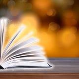 Abra o livro com luz do bokeh nas pranchas de madeira Fotografia de Stock Royalty Free