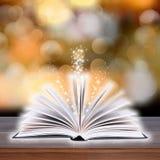 Abra o livro com luz do bokeh nas pranchas de madeira Imagens de Stock