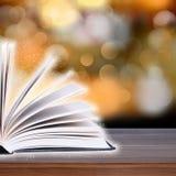 Abra o livro com luz do bokeh nas pranchas de madeira Fotos de Stock