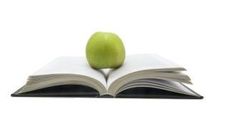 Abra o livro com a maçã nela isolou-se no fundo branco Foto de Stock