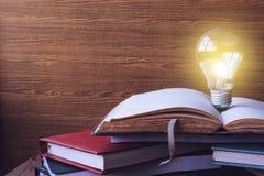 Abra o livro com os livros da ampola e do livro encadernado no fundo de madeira da parede Espaço livre para o texto Foto de Stock