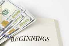 Abra o livro com a pilha de cem dólares de contas Foto de Stock