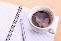 Abra o livro de nota vazio com o copo de café na tabela Fotos de Stock Royalty Free