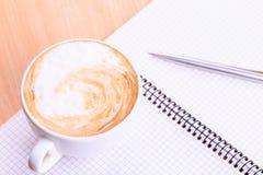 Abra o livro de nota vazio com o copo de café na tabela Fotografia de Stock Royalty Free