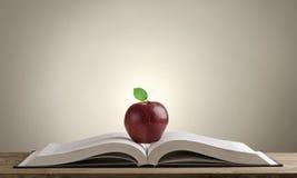 Abra o livro em uma mesa de madeira com Apple vermelho Imagem de Stock