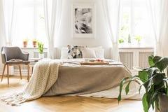 Abra o livro em uma poltrona cinzenta, de madeira por uma cama acolhedor com breakfas fotos de stock royalty free
