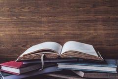 Abra o livro, livros do livro encadernado no fundo de madeira da parede Espaço livre para o texto Fotografia de Stock