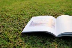 Abra o livro na grama Fotos de Stock Royalty Free