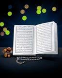 Abra o livro santamente do Corão com rosário e datas Imagens de Stock Royalty Free
