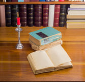 Abra o livro velho e a pilha de diversos livros pela luz de vela Fotos de Stock Royalty Free