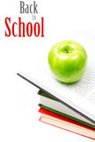 Abra o montão do livro e a maçã verde na parte superior sobre o fundo branco. Engodo Fotografia de Stock